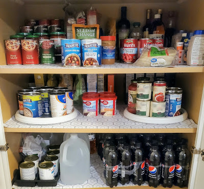 pantry shelves with canned soup, canned tomatoes, salsa, boxes of rice, boxes of noodles, and Pepsi Max bottles
