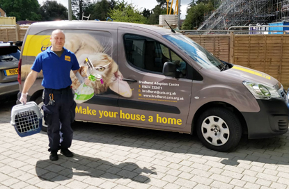 Cats Protection volunteer carrying cat carrier in front of Cats Protection van