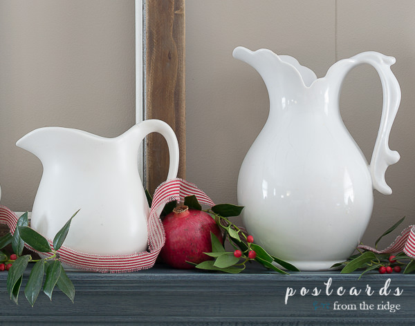 white ironstone pitchers with pomegranates and holly and red strip ribbon on a blue mantel