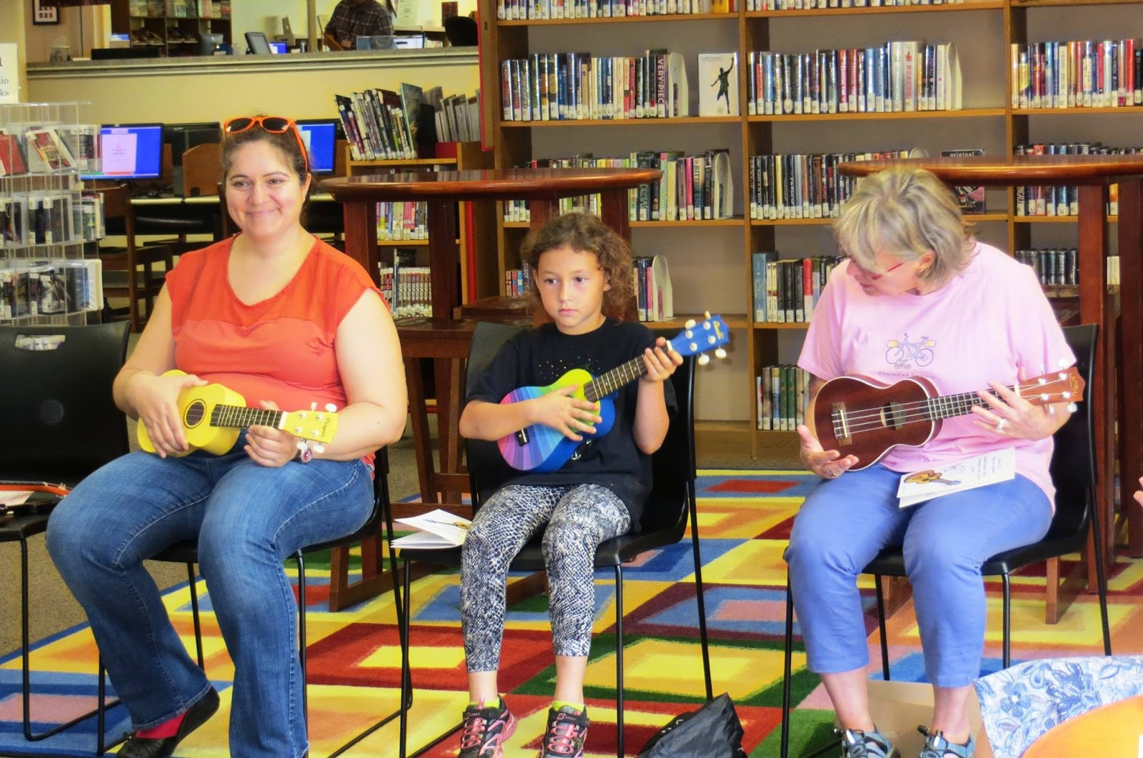 two adults and a child playing ukuleles