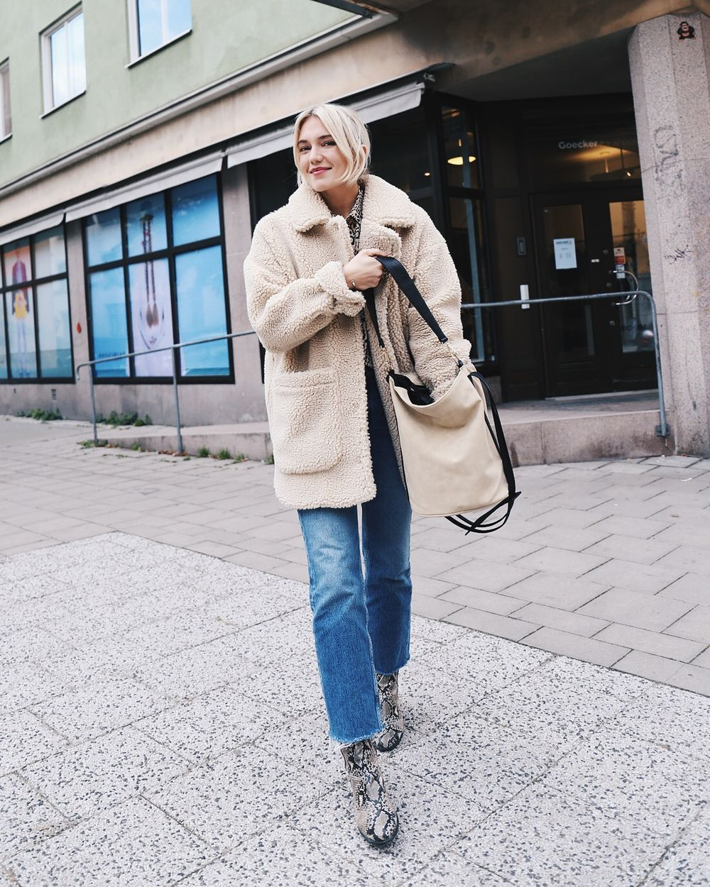Cool Shearling Jacket Winter Outfit Idea — Josefin Dahlberg look with two-toned bag, raw-hem jeans, and snake-print ankle boots