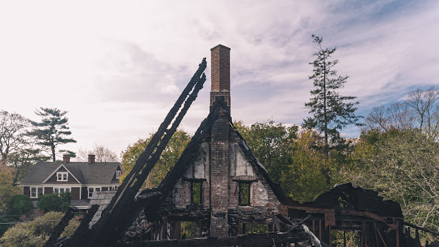 charred mansion chimney with house in background