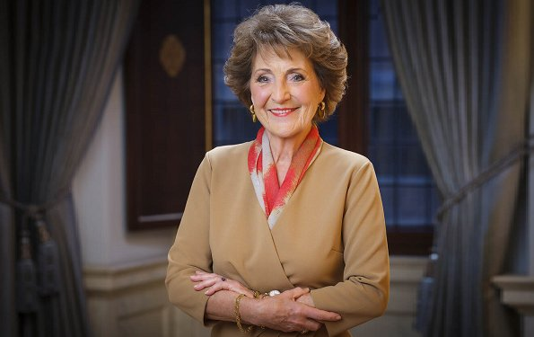 Princess Margriet wore a camel silk dress and red print scarf from Armani. green emeralds with white diamond earrings