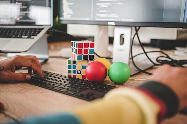 rubik di atas meja kerja di depan komputer