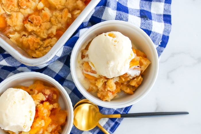 Almond Peach Dump Cake from scratch, topped with vanilla ice cream