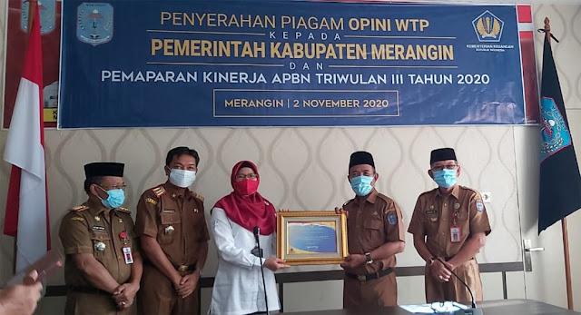 Plt Bupati Merangin saat menerima piagam penghargaan