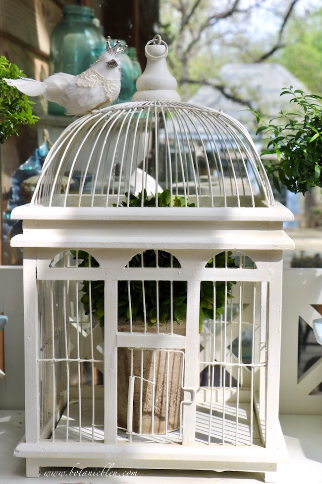 French inspired white bird cage with a domed roof and semi-circular openings is similar to French conservatories