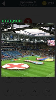 Большой стадион, на котором игра в футбол и на поле изображение символов