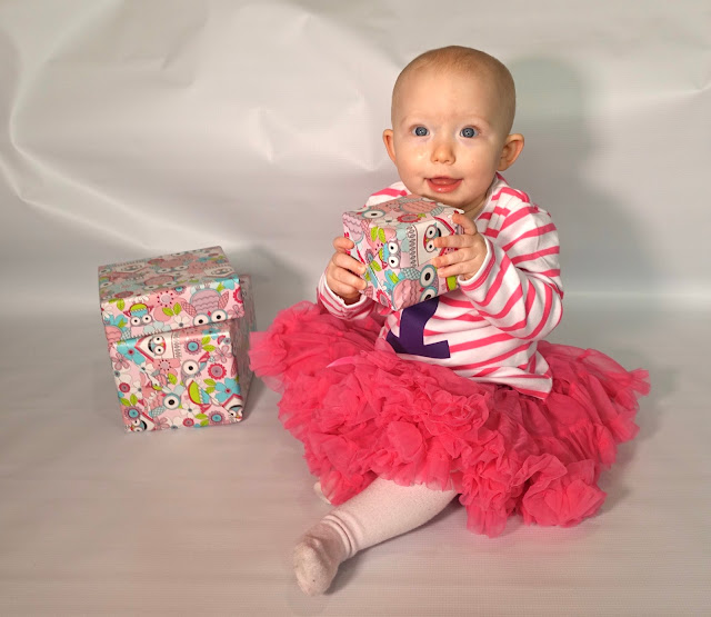 A 1 year old baby in a pink tutu, pink striped top and with presents wrapped in pink paper with owls on. Yes it's a baby girl