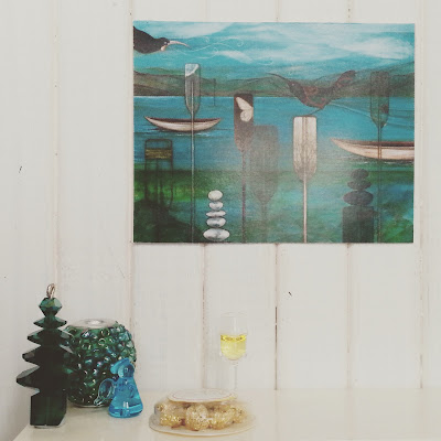 One-twelfth scale modern miniature Christmas scene on top of a sideboard with a beaded vase, tuny bead Christmas tree and glass angel next to a glass of sparking wine and a packet of chocolates. On the white paneled wall above is a picture in teals, blues and black.