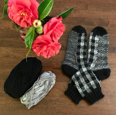 Socks knitted with DROPS Fabel Silver Fox and black laid out on table with Camellias