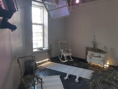 Huone, jossa erilaisia esineitä kiinnitetty seinille, lattiaan liimattu kädet