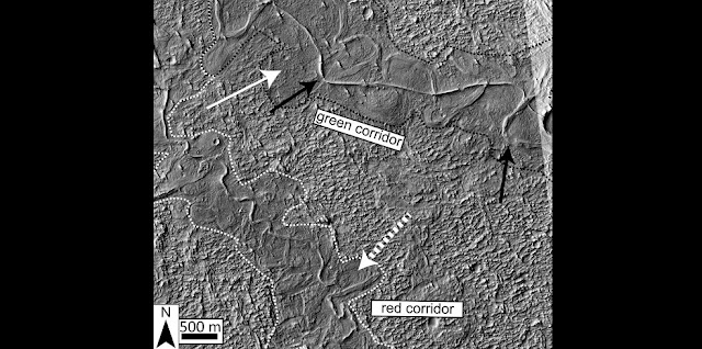 The dotted white arrow points to curved strata recording point bar growth and river migration. The boundaries of ancient valley walls are defined by textural and albedo changes and are also associated with lateral river migration. Stacked above the point bars and completely confined within the dotted white and black lines are topographically inverted river deposits outcropping as ridges (e.g., black arrow). In places (e.g., south of the dotted white arrow), the ridges run against the dotted boundaries, suggesting flow was once redirected along a valley wall. Credit: Cardenas et al., 2017.