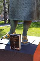 Piranesi-kirja patsaan jalustalla, patsaasta näkyy kivinen hameenhelma, sääret ja kultaiset kengät. Taustalla puisto.