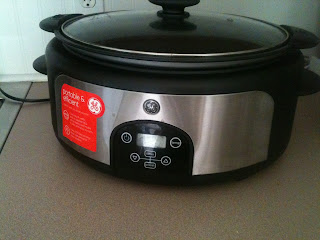 A crockpot sitting on a counter as a meal is cooked.
