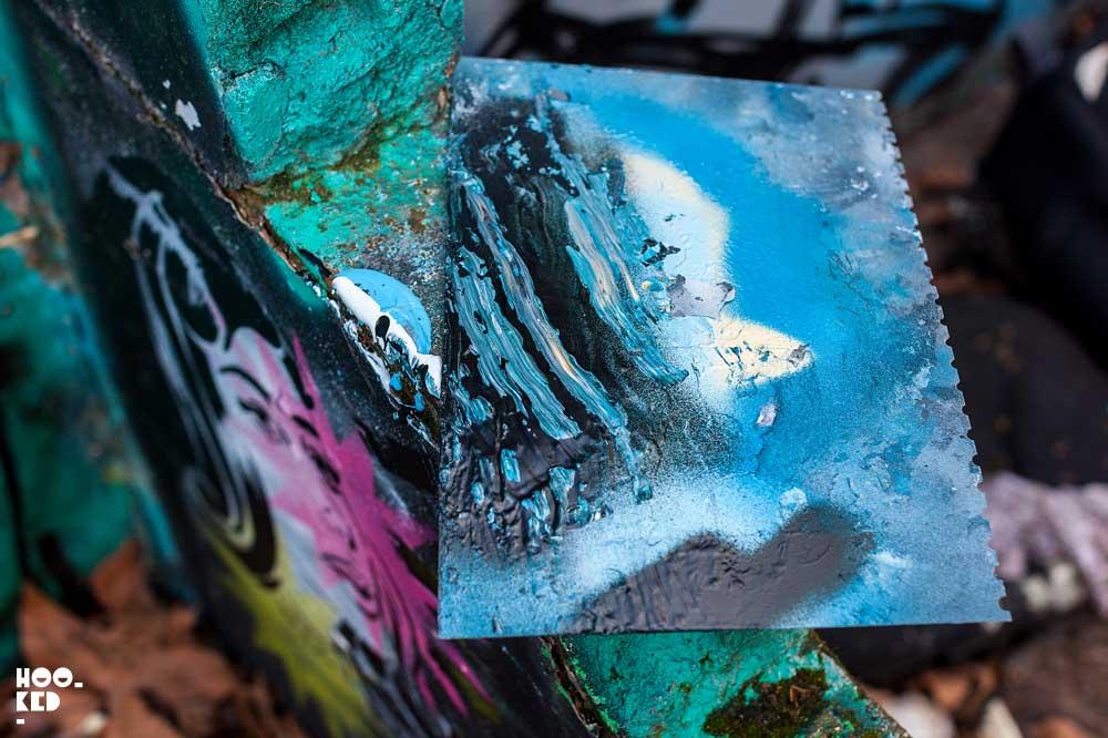 London street artist Fanakapan paints a mural in East London's Seven Star Yard car park.