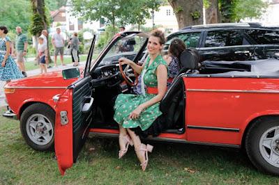 Gudrun Blümel Inhaberin von boutique new vintage in einem Kleid von boutique new vintage in einem roten oldtimer sitzend bei rocknroll im kurpark Bad Sauerbrunn