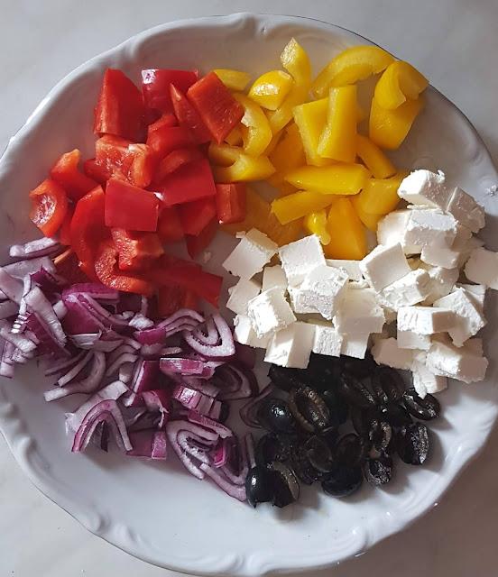 Składniki niezbędne do ugotowania ziemniaków po grecku: papryka, cebula, feta i oliwki