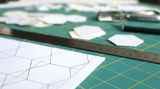Angled view of green cutting mat covered with printed papers, a metal ruler, an X-ACTO knife, a hole punch, cut hexagon templates, and paper scraps.