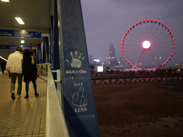"""Five Demands Not One Less"" (using symbols) graffiti on pedestrian bridge to Central Piers with the Hong Kong Observation Wheel in the background"