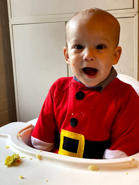 Baby boy in a high chair with mushed up sprouts and potatoes visible wearing a christmas bib