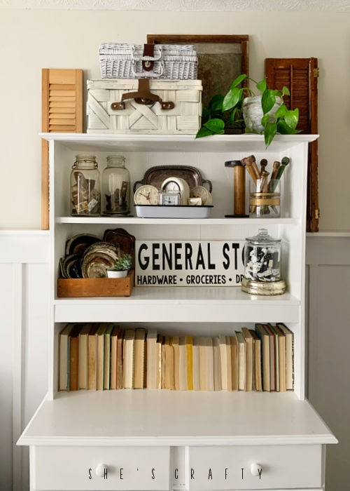 White cabinet used to display a collection of vintage objects.