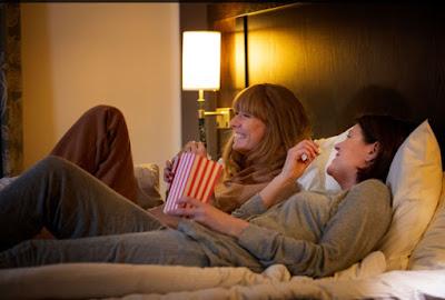 Två kvinnor halvligger i säng och ser på tv/film och äter popcorn.