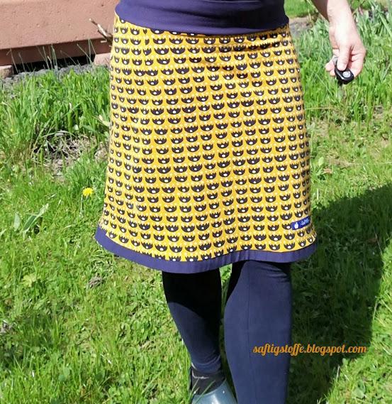 Dunkelgelber ock mit Blumen-Retromuster getragen. Frau im Garten.