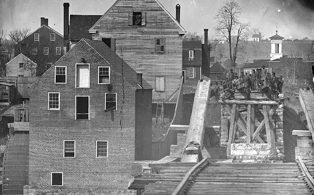 Confederate troops viewed from a distance of one mile, on the opposite side of a destroyed bridge in Fredericksburg, Virginia, by Union photographer Mathew Brady.