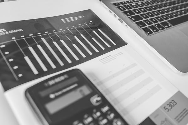 Um jornal exibindo um gráfico com uma calculadora preta sobre ele, remetendo ao investimento de renda variável