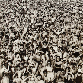 Crowd scene in black and white with people waving at the camera