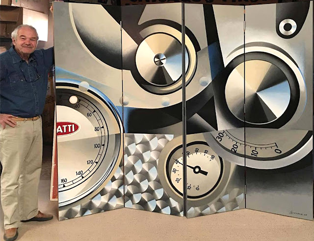 Jacques Vaucher, owner of l'art et l'automobile, stands next to one of Alain's works, A room divider detailing a classic Bugatti Dashboard.  Available at arteauto.com