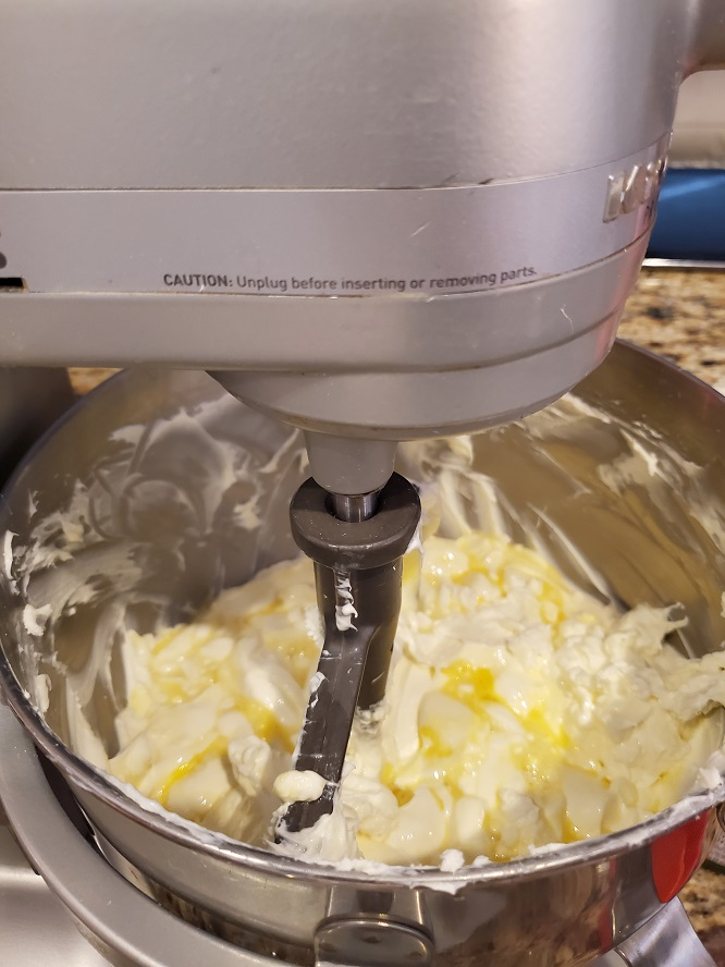 This is a silver mixing kitchen aid bowl with cheesecake batter and eggs beating with a flat beater