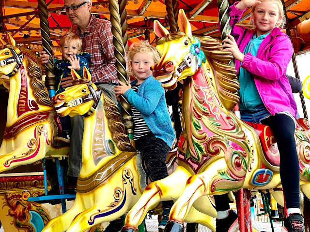 A family having fun on the gallopers carousel at Great Yarmouth Pleasure Beach Norfolk
