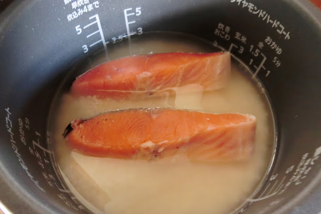 米を洗い、ザルに入れて水けを15分程度きったら炊飯器の内窯に入れて水を2合の水目盛まで入れた大さじ1水を取り除きます。【調味料】を加え、軽く全体をかき混ぜます。 キッチンペーパーで表面の水分を拭き取った鮭を入れたら通常通りにご飯を炊きます。
