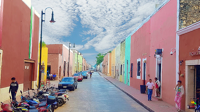 A colourful street in Mexico is all shades of pastel colours...