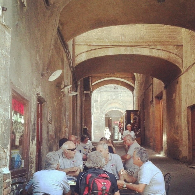 Tables under the arches in front of one of Siena's simple osterias