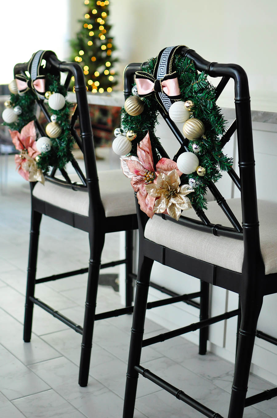 Blush pink chair wreaths with greek key accents look gorgeous on the back of these Dayna chinoiserie counter stools.