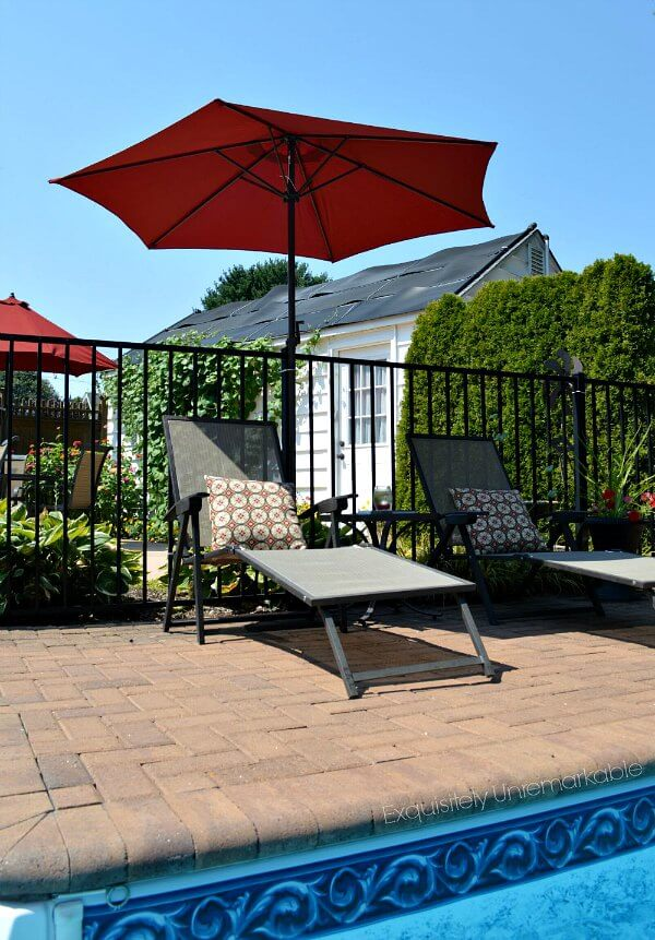 Brick pool patio with red umbrella and lounge chairs with Pillows