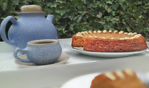 Image in the garden of Honey Almond Cake with a single slice in the foreground and a cup of tea.