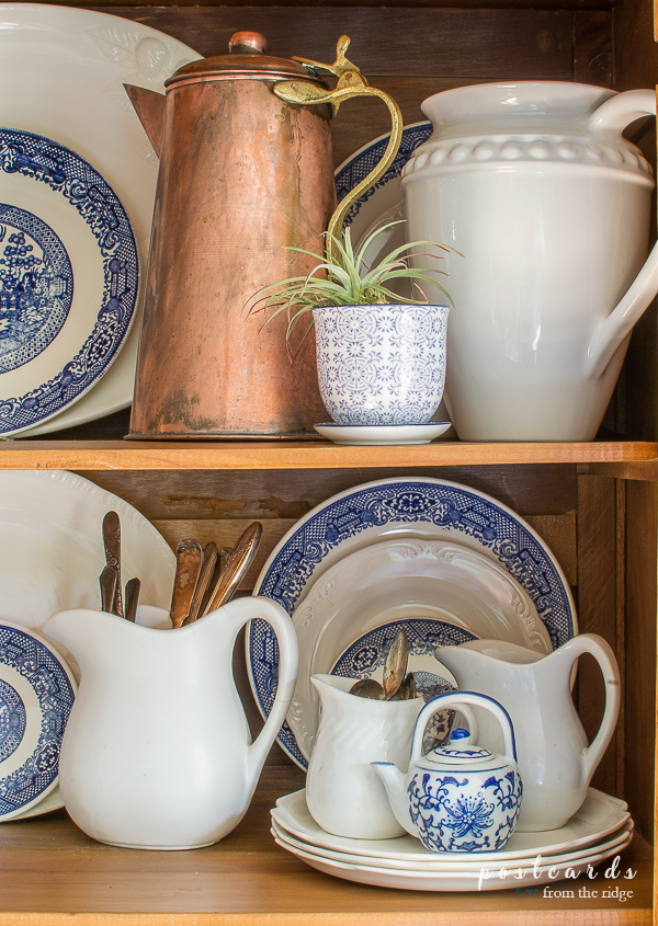 blue and white dishes with copper pitcher