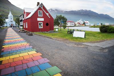 Camino de arco iris que lleva a la iglesia azul de Islandia