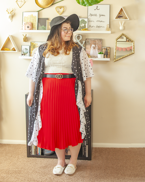 An outfit consisting of a wide brim black floppy hat, a white and black dotted wrap dress with short flowy sleeves with a black on white dot print worn as a jacket over a lace blouse tucked into a red pleated midi skirt and white mules.