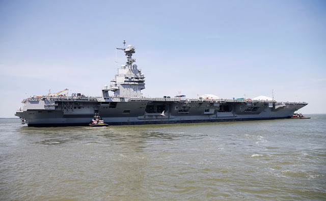 FILE PHOTO: Pre-Commissioning Unit Gerald R. Ford (CVN 78) is maneuvered by tug boats in the James River during the aircraft carrier's turn ship evolution in Newport News, Virginia, U.S. June 11, 2016.  U.S. Navy/Mass Communication Specialist Seaman Apprentice Gitte Schirrmacher/Handout via REUTERS/File Photo