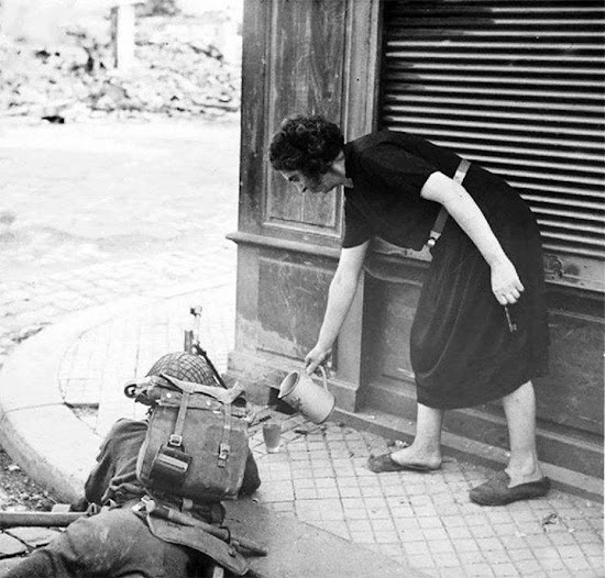French woman pouring tea for a soldier busy in a firefight