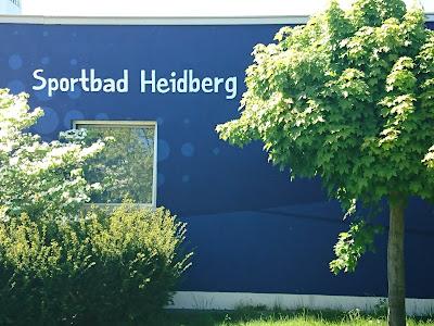 """Blaue Wand des Hallenbads mit Aufschrift """"Sportbad Heidberg."""""""