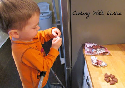 Little Dude unwrapping chocolate hearts to put on peanut butter blossom cookies