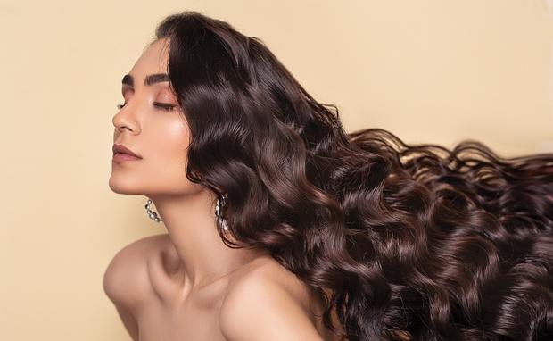 Mulher com cabelos longos e ondulados saudáveis e hidratados