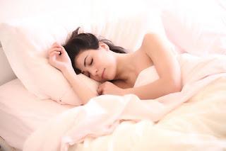 a woman sleeping on a pink mattress