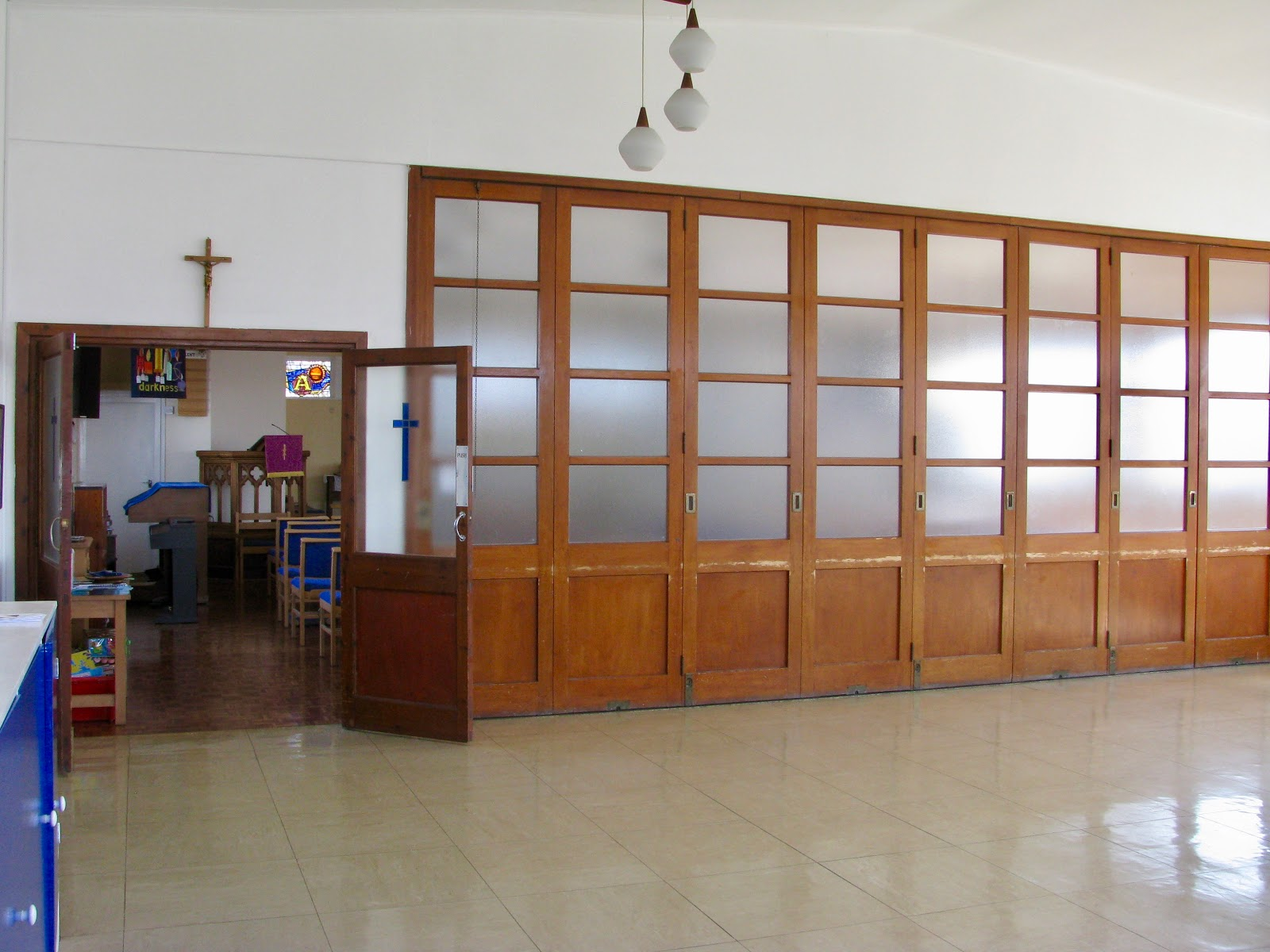 Image of entrance to church via wooden glazed doors and wooden glazed sliding doors which open to extend the church in to the hall. White walls. Sunny outside